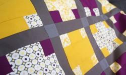 Lilla og gult patchworktæppe