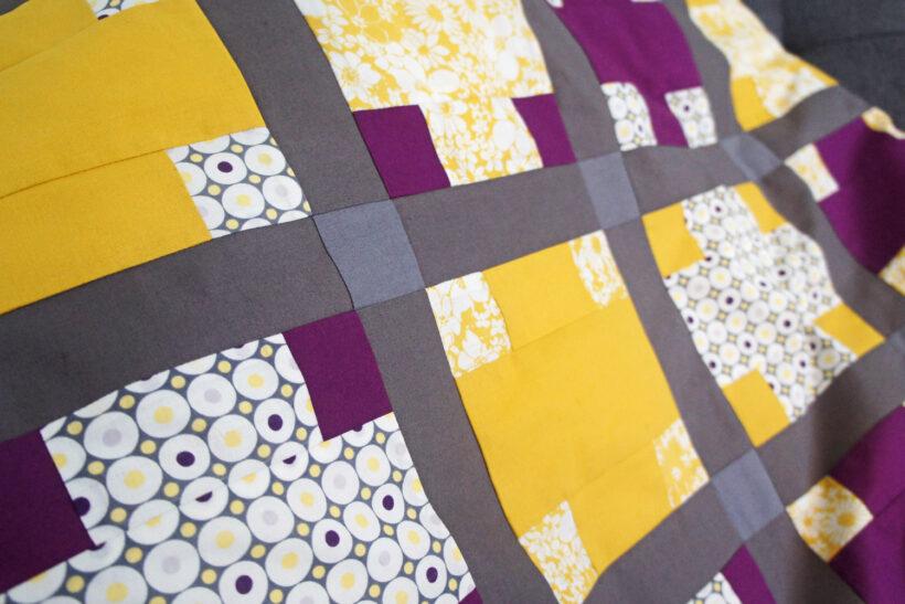 Lilla og gult patchwork babytæppe med krydser
